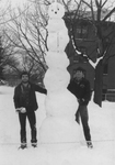 Two Students Standing Next to Snowman
