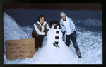 Two Women Standing Next to a Snowman